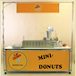 Lil' Orbits Mini Donut Kiosk: A beautiful 9' x 9' enclosed kiosk setup featuring out FSC-Series Vendor Cart with oak surround wall.