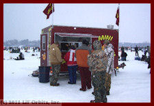 Rich Hogan makes hot mini donuts at an ice fishing festival